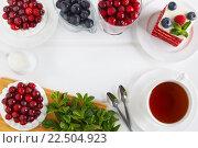 Вид сверху на безе с клюквой, торт красный бархат украшенный малиной и черникой, мяту и чашку чая на белом фоне. Стоковое фото, фотограф Козлова Анастасия / Фотобанк Лори