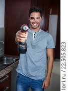 Купить «Portrait of smiling man holding cordless hand drill», фото № 22505823, снято 10 декабря 2015 г. (c) Wavebreak Media / Фотобанк Лори