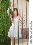 Купить «Молодая девушка в белом платье задумчиво стоит у решетки забора», фото № 22505967, снято 28 августа 2015 г. (c) Наталья Гармашева / Фотобанк Лори