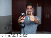 Купить «Smiling man showing thumbs up while holding cordless hand drill», фото № 22512427, снято 10 декабря 2015 г. (c) Wavebreak Media / Фотобанк Лори