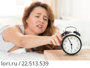 Молодая красивая женщина просыпается рано утром под звон будильника. Стоковое фото, фотограф Людмила Дутко / Фотобанк Лори