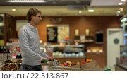 Купить «Young man with cart in store», видеоролик № 22513867, снято 29 марта 2016 г. (c) Raev Denis / Фотобанк Лори
