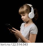 Девочка с наушниками и телефоном на темном фоне. Стоковое фото, фотограф Александр Рыбин / Фотобанк Лори