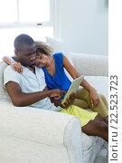 Купить «Young couple using a digital tablet in living room», фото № 22523723, снято 19 января 2016 г. (c) Wavebreak Media / Фотобанк Лори