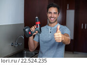 Купить «Happy man showing thumbs up while holding cordless hand drill», фото № 22524235, снято 10 декабря 2015 г. (c) Wavebreak Media / Фотобанк Лори