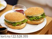 Купить «close up of two hamburgers on table», фото № 22528355, снято 22 марта 2014 г. (c) Syda Productions / Фотобанк Лори