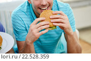 Купить «close up of happy man eating hamburger at home», фото № 22528359, снято 22 марта 2014 г. (c) Syda Productions / Фотобанк Лори