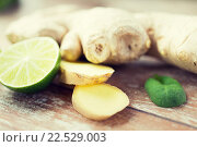 Купить «close up of ginger root and lime on wooden table», фото № 22529003, снято 28 апреля 2015 г. (c) Syda Productions / Фотобанк Лори