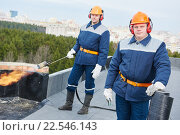 Flat roof workers with bitumen roofing felt and flame torch. Стоковое фото, фотограф Дмитрий Калиновский / Фотобанк Лори