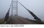 Купить «Man walking on rope bridge through the Katun river near the village of Multa», видеоролик № 22550939, снято 11 апреля 2016 г. (c) Serg Zastavkin / Фотобанк Лори