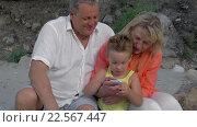 Купить «Boy and grandparents looking at photos on smartphone», видеоролик № 22567447, снято 4 февраля 2016 г. (c) Данил Руденко / Фотобанк Лори
