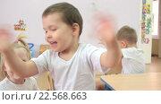 Купить «Дети сидят за столом и размахивают руками», видеоролик № 22568663, снято 7 апреля 2016 г. (c) Алексндр Сидоренко / Фотобанк Лори