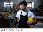 Carpenter texting someone and holding his helmet. Стоковое фото, агентство Wavebreak Media / Фотобанк Лори
