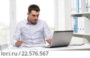 Купить «busy businessman with laptop and papers in office», видеоролик № 22576567, снято 9 июля 2015 г. (c) Syda Productions / Фотобанк Лори