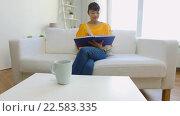 Купить «smiling young asian woman reading book at home», видеоролик № 22583335, снято 11 марта 2016 г. (c) Syda Productions / Фотобанк Лори