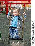 Купить «Девочка качается на качелях на детской площадке», фото № 22583907, снято 9 апреля 2016 г. (c) Олег Шеломенцев / Фотобанк Лори