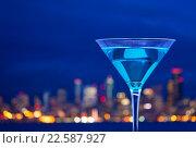 Купить «Крупным планом бокал мартини на фоне огней большого города», фото № 22587927, снято 10 января 2016 г. (c) Сергей Новиков / Фотобанк Лори