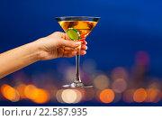 Купить «Бокал мартини с фишками в руке на фоне вечернего города», фото № 22587935, снято 10 января 2016 г. (c) Сергей Новиков / Фотобанк Лори