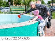 Бабушка помогает внучке налить в ведерко воды из фонтана. Стоковое фото, фотограф Анна Кирьякова / Фотобанк Лори