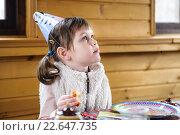 Девочка в праздничном колпаке сидит за столом и смотрит наверх. Стоковое фото, фотограф Анна Кирьякова / Фотобанк Лори