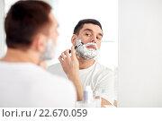 Купить «man shaving beard with razor blade at bathroom», фото № 22670059, снято 15 января 2016 г. (c) Syda Productions / Фотобанк Лори