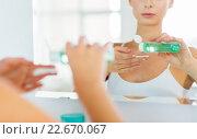 Купить «young woman with lotion washing face at bathroom», фото № 22670067, снято 13 февраля 2016 г. (c) Syda Productions / Фотобанк Лори