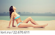 Купить «happy woman tanning in bikini over swimming pool», фото № 22670611, снято 14 апреля 2015 г. (c) Syda Productions / Фотобанк Лори