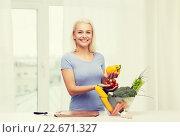 Купить «smiling young woman cooking vegetables at home», фото № 22671327, снято 26 апреля 2015 г. (c) Syda Productions / Фотобанк Лори
