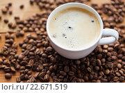 Купить «close up coffee cup and grains on wooden table», фото № 22671519, снято 7 апреля 2016 г. (c) Syda Productions / Фотобанк Лори