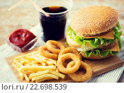 Купить «close up of fast food snacks and drink on table», фото № 22698539, снято 21 мая 2015 г. (c) Syda Productions / Фотобанк Лори