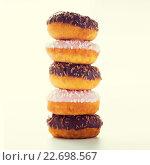 Купить «close up of glazed donuts pile over white», фото № 22698567, снято 21 мая 2015 г. (c) Syda Productions / Фотобанк Лори