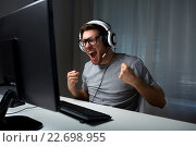 Купить «man in headset playing computer video game at home», фото № 22698955, снято 12 марта 2016 г. (c) Syda Productions / Фотобанк Лори