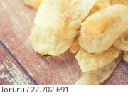 Купить «close up of crunchy potato crisps on wooden table», фото № 22702691, снято 22 мая 2015 г. (c) Syda Productions / Фотобанк Лори