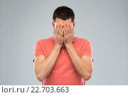 man in t-shirt covering his face with hands. Стоковое фото, фотограф Syda Productions / Фотобанк Лори