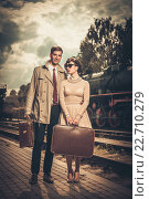 Купить «Vintage style couple with suitcases on train station platform», фото № 22710279, снято 10 сентября 2013 г. (c) Andrejs Pidjass / Фотобанк Лори