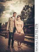 Купить «Vintage style couple with suitcases on train station platform», фото № 22710279, снято 10 сентября 2013 г. (c) Andrejs Pidjass / Фотобанк Лори