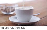 Купить «cream pouring to coffee cup on wooden table», видеоролик № 22710327, снято 15 апреля 2016 г. (c) Syda Productions / Фотобанк Лори