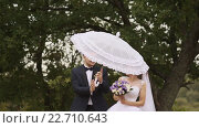 Купить «Жених ходит вокруг невесты с белым зонтиком», видеоролик № 22710643, снято 12 апреля 2016 г. (c) Mikhail Davidovich / Фотобанк Лори
