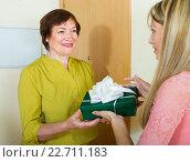 Купить «Mature neighbor presenting gift to young girl», фото № 22711183, снято 23 мая 2014 г. (c) Яков Филимонов / Фотобанк Лори