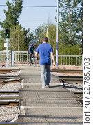 Купить «Человек идет по пешеходному переходу через железнодорожные пути на зеленый разрешающий сигнал светофора», фото № 22785703, снято 2 мая 2016 г. (c) Лариса Капусткина / Фотобанк Лори