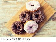 Купить «close up of glazed donuts pile on table», фото № 22813527, снято 21 мая 2015 г. (c) Syda Productions / Фотобанк Лори