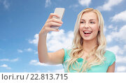 Купить «smiling young woman taking selfie with smartphone», фото № 22813715, снято 13 февраля 2016 г. (c) Syda Productions / Фотобанк Лори