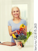 Купить «smiling young woman cooking vegetables at home», фото № 22815263, снято 26 апреля 2015 г. (c) Syda Productions / Фотобанк Лори