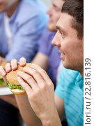Купить «close up of friends eating hamburgers at home», фото № 22816139, снято 22 марта 2014 г. (c) Syda Productions / Фотобанк Лори