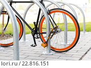 Купить «close up of bicycle locked at street parking», фото № 22816151, снято 30 мая 2015 г. (c) Syda Productions / Фотобанк Лори