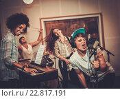 Купить «Multiracial music band performing in a recording studio», фото № 22817191, снято 29 июля 2015 г. (c) Andrejs Pidjass / Фотобанк Лори