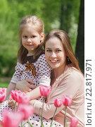 Счастливая женщина сидит в парке с девочкой, у которой приколота на груди георгиевская лента. Стоковое фото, фотограф Юлия Кузнецова / Фотобанк Лори