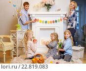 Купить «Cheerful family siting near a fireplace on cozy carpet and playing with cute bunny.», фото № 22819083, снято 3 февраля 2016 г. (c) Andrejs Pidjass / Фотобанк Лори
