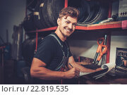 Купить «Professional car mechanic at his workplace preparing checklist in auto repair service.», фото № 22819535, снято 26 февраля 2016 г. (c) Andrejs Pidjass / Фотобанк Лори