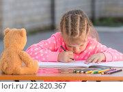 Купить «Обиженная девочка сгорбившись рисует рисунок во дворе дома», фото № 22820367, снято 25 апреля 2016 г. (c) Иванов Алексей / Фотобанк Лори